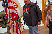 "13 JULY 2012 - FT DEFIANCE, AZ: Veterans present the American flag during a special veterans' service at the 23rd annual Navajo Nation Camp Meeting in Ft. Defiance, north of Window Rock, AZ, on the Navajo reservation. Preachers from across the Navajo Nation, and the western US, come to Navajo Nation Camp Meeting to preach an evangelical form of Christianity. Evangelical Christians make up a growing part of the reservation - there are now more than a hundred camp meetings and tent revivals on the reservation every year. The camp meeting in Ft. Defiance draws nearly 200 people each night of its six day run. Many of the attendees convert to evangelical Christianity from traditional Navajo beliefs, Catholicism or Mormonism. ""Camp meetings"" are a form of Protestant Christian religious services originating in Britain and once common in rural parts of the United States. People would travel a great distance to a particular site to camp out, listen to itinerant preachers, and pray. This suited the rural life, before cars and highways were common, because rural areas often lacked traditional churches. PHOTO BY JACK KURTZ"