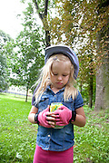Tired Polish child with can of soda pink fingerless bicycle gloves and helmet age 4. Paderewski Park Rzeczyca Central Poland