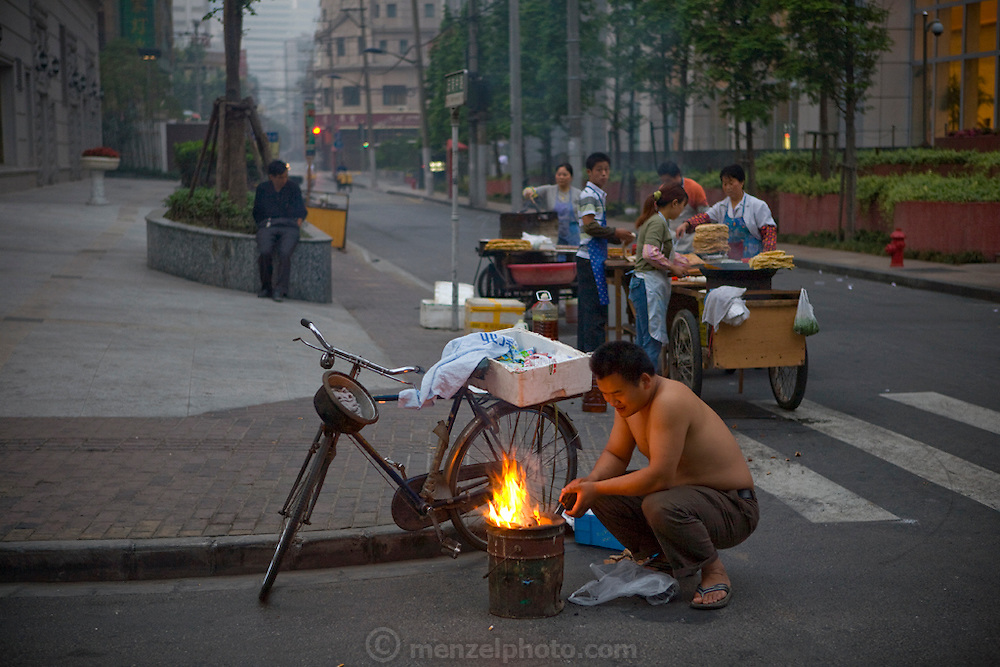 Vendors prepare to sell breakfast at a street corner in Shanghai, China.