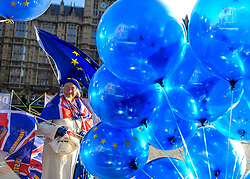 © Licensed to London News Pictures. 13/12/2018. Westminster, London, UK. Remain activist Lynne Hall, 81 holds EU and Union Jack flags outside Westminster Palace in a solitary protest a day after Teresa May survived a no confidence vote. Photo credit Guilhem Baker/LNP