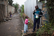 Stephanie Ndunge, 3, brushes her teeth with her father, Michael Nzuli Mwamati, in the Kariobangi District in Nairobi, Kenya. Families in Kariobangi often have to skimp on meals when they are not able to earn enough in a day to purchase such basic food items as flour and corn. Michael is a member of the Samba Youth Group, a project started by CRS and the local Catholic Church to provide job opportunities and a support forum for youth in Kariobangi.  Samba has started a garbage collection group, a car washing station and community policing.