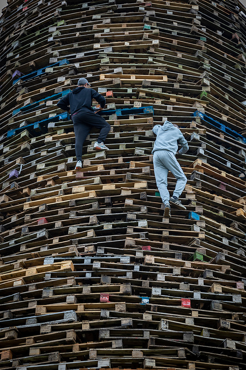 Two men climb the high bonfire in Larne, in order to fly a flag. In preparation of the midnight lighting of the massive fire. Belfast, NI, 2021.