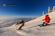 Skier and snowboarder down the fresh groom on Inspiration at Whitefish Mountain Resort in Whitefish, Montana, USA model released