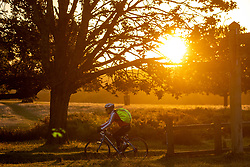 Licensed to London News Pictures. 06/10/2021. London, UK. After yesterday's torrential rains and flooding, a cyclist enjoys a glorious sunrise in Richmond Park south-west London this morning as weather forecasters predict a mild few days ahead with highs of 20c. Photo credit: Alex Lentati/LNP