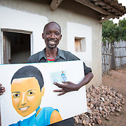 CAPTION: Stanislas beams with pride as he holds his daughter's self portrait, painted using her passport photo for reference. During her next holiday from boarding school, she plans to paint her brother's picture next to hers. Stanislas feels his daughter shows true promise as an artist, and he is keen to support her in this. LOCATION: Rushikiri Village, Kimuna Cell, Rusatira Sector, Huye District, South Province, Rwanda. INDIVIDUAL(S) PHOTOGRAPHED: Stanislas Iriboneye.