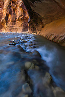 The Virgin River carves its way through the Narrows in Zion National Park as the sun illuminates the surrounding rock walls.