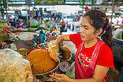 """26 SEPTEMBER 2012 - BANGKOK, THAILAND: A vendor sells different home made curry pastes in Khlong Toey Market in Bangkok. The curry pastes form the base of Thailand's famous curries. Khlong Toey (also called Khlong Toei) Market is one of the largest """"wet markets"""" in Thailand. The market is located in the midst of one of Bangkok's largest slum areas and close to the city's original deep water port. Thousands of people live in the neighboring slum area. Thousands more shop in the sprawling market for fresh fruits and vegetables as well meat, fish and poultry.     PHOTO BY JACK KURTZ"""