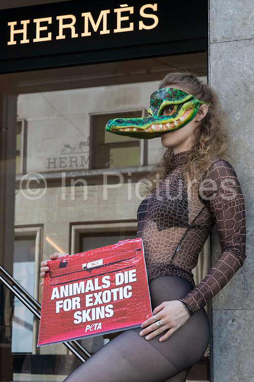 A PETA supporter wearing a Venetian crocodile mask poses outside the Hermès store in New Bond Street in protest against the luxury fashion houses use of exotic skins on 8th September 2021 in London, United Kingdom. PETAs campaign was launched following the release of video footage by Kindness Project showing crocodiles being mutilated, electrocuted, stabbed and shot on farms in Australia with ties to Hermès and PETA are calling on the fashion brand to cease using exotic skins for their products.