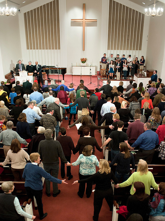 """Parishioners reach for each other's hands as they sing the song """"We Shall Overcome"""" at the end of an interfaith service at Newtown Congregational Church in Newtown, Conn., Sunday, Jan. 20, 2013. (AP Photo/Jessica Hill)"""