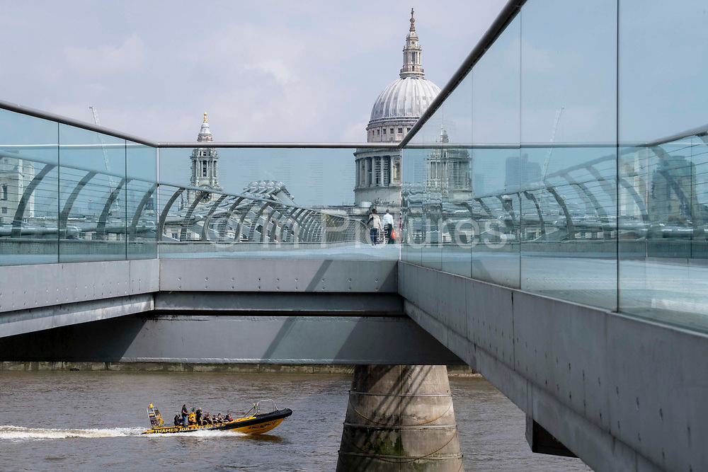 With the dome of St Pauls cathedral in the distance, a Thames Rib Experience boat speeds on the river Thames and beneath the Millennium Bridge, on 24th June 2021, in London, England. Londons newest river crossing for 100-plus years coincided with the Millennium. It was hurriedly finished and opened to the public on 10 June 2000 when an estimated 100,000 people crossed it to discover the structure oscillated so much that it was forced to close 2 days later. Over the next 18 months designers added dampeners to stop its wobble but it already symbolised what was embarrassing and failing in British pride. Now the British Standard code of bridge loading has been updated to cover the swaying phenomenon, referred to as Synchronous Lateral Excitation.