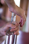 Capping bottles of Back River Gin by hand, Sweetgrass Winery, Union, Maine.