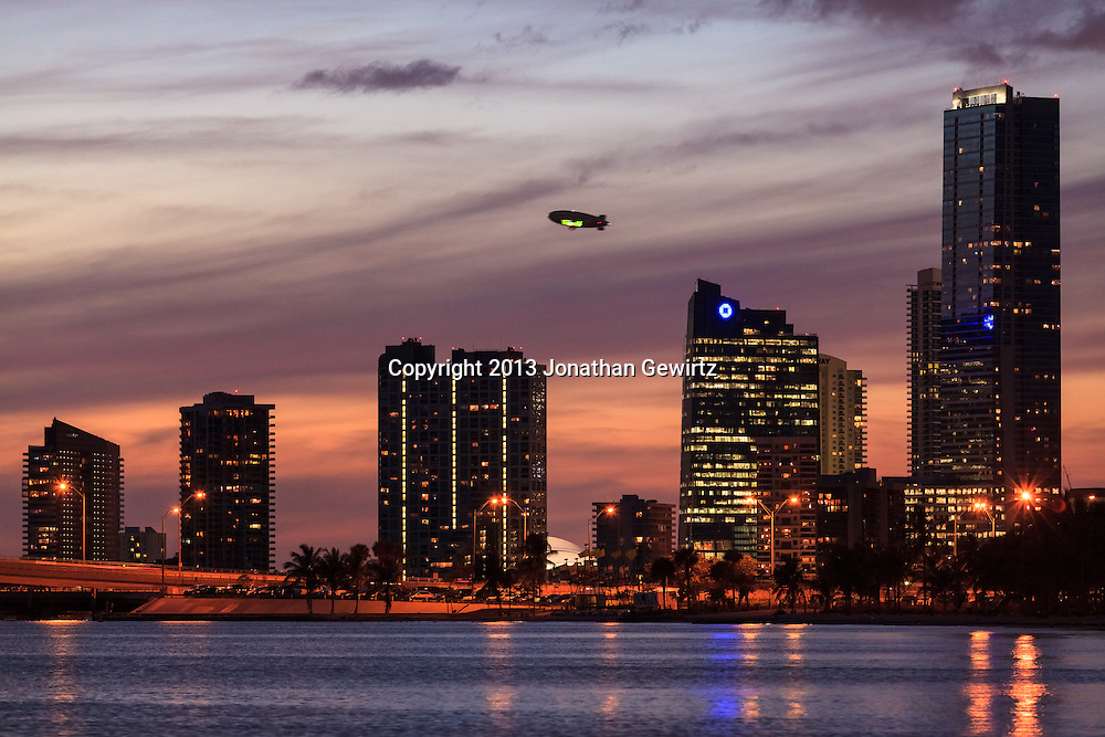A Goodyear blimp flies behind buildings on Miami's Brickell Avenue at dusk with the Rickenbacker Causeway in the foreground. WATERMARKS WILL NOT APPEAR ON PRINTS OR LICENSED IMAGES.
