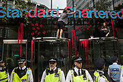 Two environmental activists from Extinction Rebellion spread blood-red paint across the facade of Standard Chartered bank during a Blood Money March through the City of London on 27th August 2021 in London, United Kingdom. Extinction Rebellion were intending to highlight the £23bn which they say Standard Chartered has invested in fossil fuels since the Paris Agreement whilst calling on the UK government to cease all new fossil fuel investment with immediate effect.
