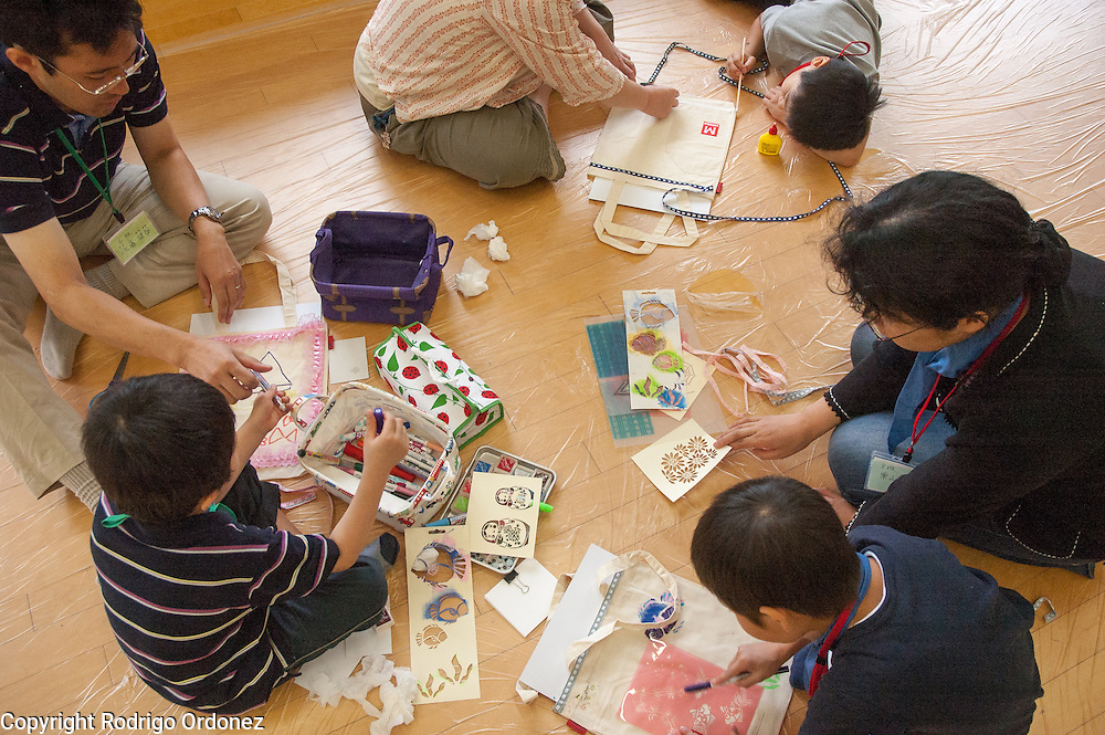Parents and their children participate in handicrafts activities during a summer camp for children from Fukushima, Japan.