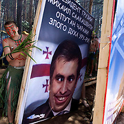 """Pro-Putin Nashi youths putting up a poster demonising Georgian President Mikheil Saakashvili during a summer camp on Lake Seliger in Russia. The poster reads: """"President of Georgia Mikheil Saakashvili is ensnared by charms of evil spirit Uru-ru!"""" The yearly camp, organised by the nationalistic group, trains youth in political activism. Georgia, a former Soviet state, has taken a tough anti-Russian stance since Saakashivili took power."""