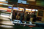 SHOT 10/23/2007 - Passengers ride the Powell-Hyde cable car near the Powell and Market turntable in San Francisco, Ca. one evening. The City and County of San Francisco is the fourth most populous city in California and the fourteenth-most populous in the United States. San Francisco is a popular international tourist destination renowned for its steep rolling hills, an eclectic mix of Victorian and modern architecture, its large LGBT (lesbian, gay, bisexual, and transgender) population, and its chilly summer fog and mild winters. Famous landmarks include Union Square, Pacific Heights, Russian Hill, Fisherman's Wharf, North Beach and Chinatown. The best known existing cable car system is the San Francisco cable car system in the city of San Francisco, California. This is the oldest and biggest cable car system in permanent operation, and it is the only system to still operate in the traditional manner with manually operated cars running in street traffic. The San Francisco cable car system is the world's last permanently operational manually-operated cable car system, and is now an icon of the city of San Francisco in California. The cable car system forms part of the intermodal urban transport network operated by the San Francisco Municipal Railway, or Muni as it is better known. Cable cars operate on two routes from downtown near Union Square to Fisherman's Wharf, and a third route along California Street. While the cable cars are used to a certain extent by commuters, their low speed, small service area, and premium fares for single rides make them primarily a tourist attraction.(Photo by Marc Piscotty © 2007)