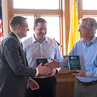 GGEDC President Tommy Haws, left, awards Martin O'Malley, general manager of Gallup Land Partners, right, and Jake Bracken, CEO of Gallup Land Partners, center, with an Excellence in Business 2019 award at a luncheon Tuesday, May 7 in Gallup.