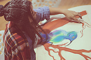 Young female artist finger painting with pastel paints