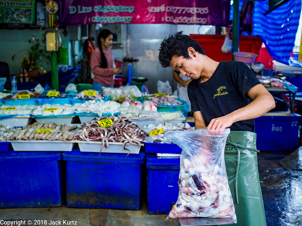12 JULY 2018 - SAMUT PRAKAN, SAMUT PRAKAN, THAILAND:  A man weights a bulk bag of seafood in the Pak Nam market in Sumut Prakan. Fish consumption recently hit a record high according to a report published this week by the United Nations Food and Agriculture Organization. The FAO reported that global fish production peaked at about 171 million tonnes in 2016, 47 percent of it from fish farming. The FAO also reported that global fish consumption between 1961 and 2016 was rose nearly twice as fast as population growth. In 2015, fish accounted for about 17 percent of the animal protein consumed globally. This has ramifications for Thailand, which has one of the world's largest fish and seafood industries. About 90% of Thailand's seafood production is exported, which accounts for about 4% of Thailand's exports.   PHOTO BY JACK KURTZ