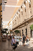 Fabric spread over buildings to provide shade in busy shopping street called Velazquez in central Seville, Spain