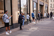to comply with the distance rules during the Corona pandemic, customers are waiting in front of the Apple Store on Schildergasse, Cologne, Germany.<br /> <br /> zur Einhaltung der Abstandsregeln waehrend der Corona-Pandemie warten Kunden vor dem Apple Store in der Schildergasse, Koeln, Deutschland.