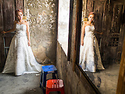 17 MARCH 2015 - BANGKOK, THAILAND: A woman poses for prewedding photos in the old Customs House in Bangkok. With its evocative architecture and turn of the century mood, the Customs House is a popular setting for wedding photos and portraits. The old Customs House was once the financial gateway to Thailand (before 1932 called Siam). It was designed by an Italian architect in the 1880s. In the 1950s, customs moved to new, more modern building and the Customs House became the headquarters for the Marine firefighters. The firefighters now live in the decrepit buildings with their families.    PHOTO BY JACK KURTZ