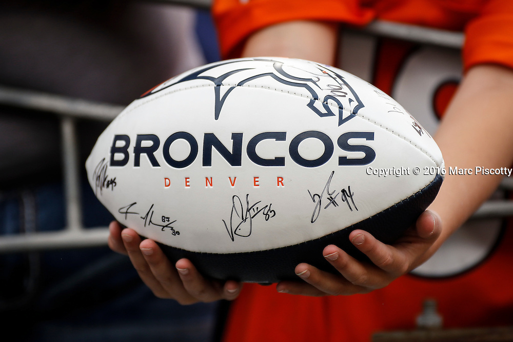 A young Denver Broncos fan holds out a football hoping to have it signed by a Broncos player as they warm up before playing against the LA Rams during a preseason game at Sports Authority Field at Mile High in Denver, CO, August 27, 2016. (Photo by Marc Piscotty / © 2016)