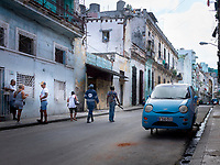 Blue car on jacks without wheels on a street in Havana.