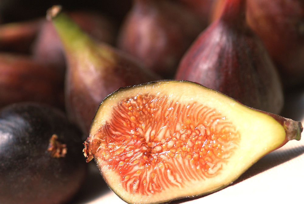 Close up selective focus photograph of some Black Mission Figs with one cut open to expose the fruit
