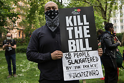 An activist holds a placard and a sign referring to police killings in Jacarezinho (Rio de Janeiro) at a Kill The Bill National Day of Action in protest against the Police, Crime, Sentencing and Courts (PCSC) Bill 2021 on 29th May 2021 in London, United Kingdom. The PCSC Bill would grant the police a range of new discretionary powers to shut down protests, including the ability to impose conditions on any protest deemed to be disruptive to the local community, wider stop and search powers and sentences of up to 10 years in prison for damaging memorials.