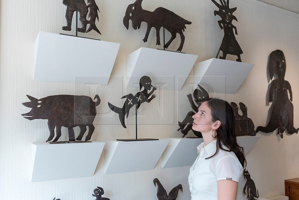 """© Licensed to London News Pictures. 02/10/2018. LONDON, UK. A staff member views sculptures by Georges Liautaud. Preview of """"Art + Revolution in Haiti"""", an exhibition at The Gallery of Everything in Chiltern Street.  The exhibition, which coincides with Frieze Week, explores when Surrealism arrived in the former slave colony in 1945.  Works from artists from le Centre d'Art d'Haiti and from the personal collection of Andre Breton, the founder of Surrealism, are on display until 11 November 2018.  Photo credit: Stephen Chung/LNP"""