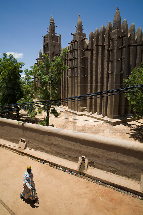 """A man dressed with a """"bubu"""" passes by Mopti's Great Mosque. At the confluence of the Niger and the Bani rivers, between Timbuktu and Ségou, Mopti is the second largest city in Mali, and the hub for commerce and tourism in this west-african landlocked country."""
