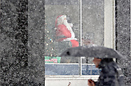 Middletown, NY - A mechanical Santa waves from the window of a business as a man walks by with an umbrella during a winter storm on Dec. 19, 2008.
