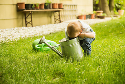 Little boy looking into watering can at garden