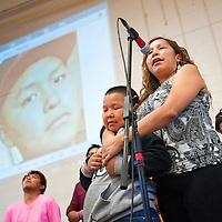 041913       Cable Hoover<br /> <br /> Malena Begaye and her say a prayer beneath a projection of her brother Tyler Claw during a fundraiser at Miyamura High School Friday. Claw is being treated for leukemia in Denver.
