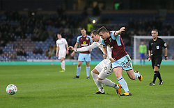 Leeds United's Pierre-Michel Lasogga (left) and Burnley's Kevin Long battle for the ball during the Carabao Cup, third round match at Turf Moor, Burnley.