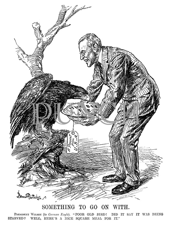 """Something to Go on With. President Wilson (to German eagle). """"Poor old bird! Did it say it was being starved? Well, here's a nice square meal for it."""""""