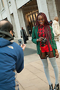 A photographer wearing red gets photographed outside the fashion show.