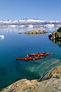 EAST GREENLAND, Sea Kayaking, Johan Peterson Fjord, paddlers in kayaks, iceberg