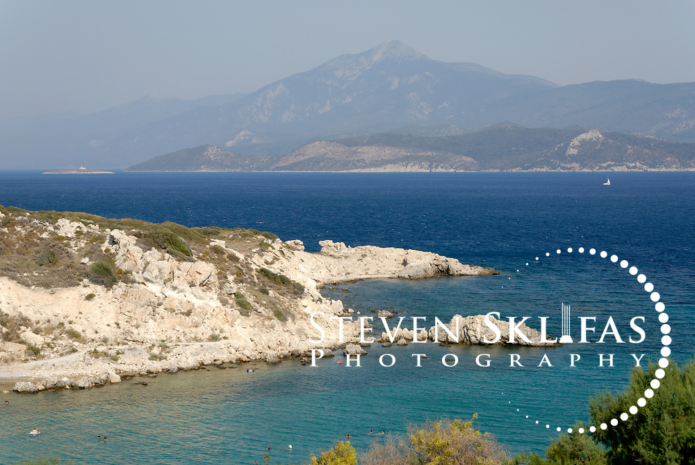 Samos. Greece. Seascape of the Aegean Sea and small pebbly beach near the town of Pythagoreio. In the distance are the mountains of western Turkey.
