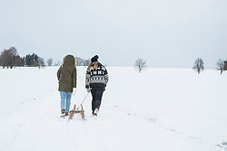 Two teenage girls with sled in snowy landscape in winter, Bavaria, Germany