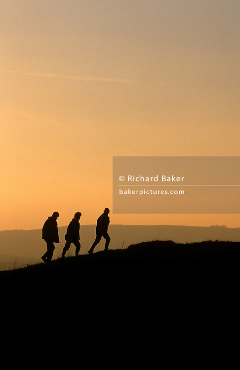 Three silhouetted walkers (two women and one male) near the top of a hill near the village of Churchill, North Somerset, England. The image has only three tones, graduating from dark at the bottom, becoming lighter to the top. It is late in the day and the light is soft and warm in colour and the friends make their way up the gradient in single-file, each striding with legs apart as they climb the hill forming part of the Mendips. It is a scene of tranquillity, the landscape is peaceful and unspoilt for outdoor countryside pursuits like walking, one of the fastest-growing leisure activities in Britain for people who take advantage of rural England.