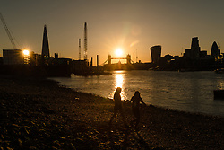 © Licensed to London News Pictures. 25/05/2017. LONDON, UK.  Two women walk along the foreshore at low tide as the sun sets on the River Thames behind Tower Bridge, St Paul's Cathedral and City of London skyscrapers after a day of hot and sunny weather in London. Photo credit: Vickie Flores/LNP