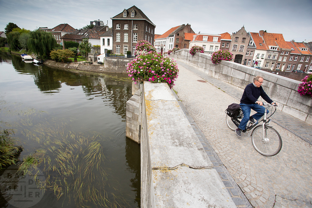 In Roermond rijden fietsers over de Maria Theresiabrug over de Roer. De brug wordt ook wel de Stenen brug genoemd en is gebouwd in 1771.<br /> <br /> Cyclists riding at the Maria Theresia Bridge in Roermond. The bridge is also known as the Stenen Brug and is built in 1771.