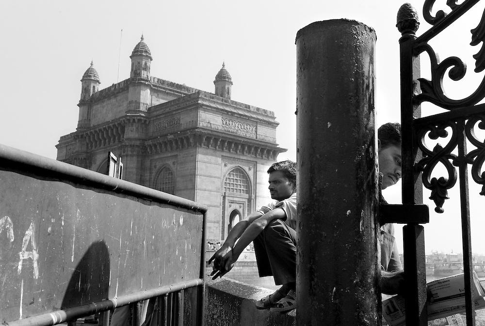 Men await near the Gateway of India monument in Mumbai, India.