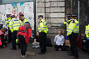 Metropolitan Police officers detain environmental activists from Extinction Rebellion after a vintage bus was used as a base to block a road junction to the south of London Bridge on the ninth day of Impossible Rebellion protests on 31st August 2021 in London, United Kingdom. Extinction Rebellion are calling on the UK government to cease all new fossil fuel investment with immediate effect.