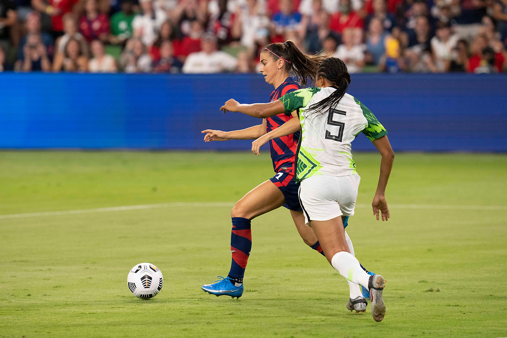 Forward ALEX MORGAN (13) of the USA team beats ONOME EBI (5) of Nigeria for the ball as the US Women's National Team (USWNT) beats Nigeria, 2-0 in the inaugural match of Austin's new Q2 Stadium. The U.S. women's team, an Olympic favorite, is wrapping up a series of summer matches to prep for the Tokyo Games.