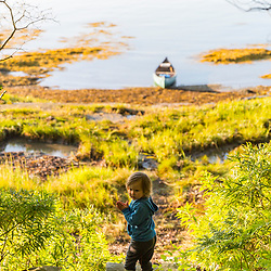 A young girl explores the shoreline after a night of camping on Lanes Island in Casco Bay. Yarmouth, Maine.