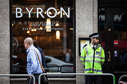 © Licensed to London News Pictures. 01/08/2016. London, UK. Police stand guard outside the Holborn branch of Byron Burger in central London ahead of a planned demonstration. The chain has received criticism after 35 of its staff were arrested for immigration offences last week. Photo credit: Rob Pinney/LNP