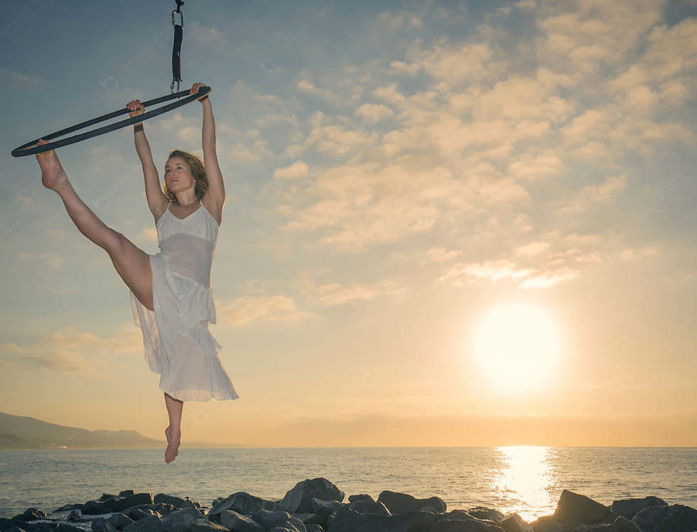 Aerial ring dancer over the sea at sunrise
